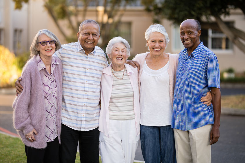 Portrait of cheerful senior people standing with arms around outside nursing home